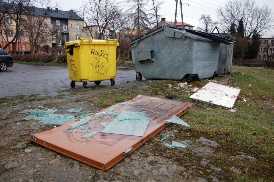 Pod śmietnikami leżą stare drzwi i wersalki