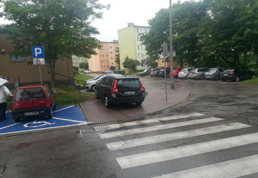 Piesi przeciskają się między parkującymi samochodami